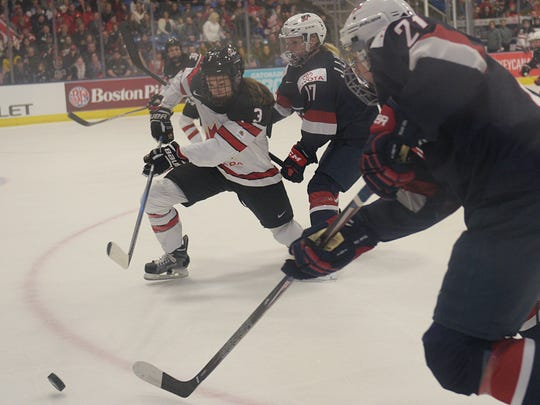 Team USA's Hilary Knight (21), Jocelyne Lamoureux (17), and Canada's Jocelyne Larocque (3) battle for the puck.