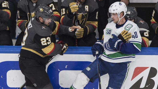 Vegas Golden Knights' Alec Martinez (23) gets his glove taken by Vancouver Canucks' Elias Pettersson (40) during the third period of Game 2 of a second-round playoff series Tuesday in Edmonton, Alberta.