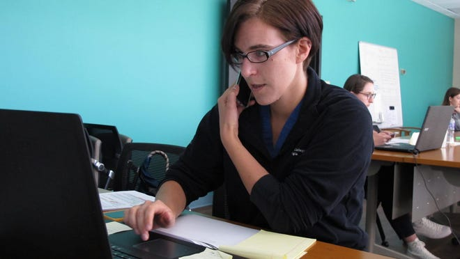 Medical student Rebecca DeCarlo conducts a follow-up interview with a person being monitored by the Georgia Department of Public Health for infection or exposure to the coronavirus at the state agency's district office in Savannah in April.