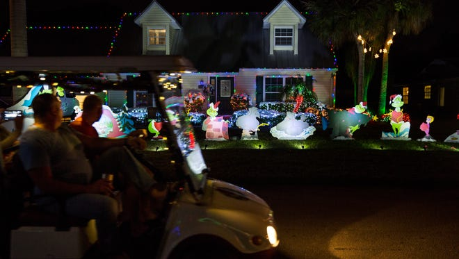 People ride a golf cart through the Victoria Park neighborhood to look at all the Christmas decorations on Thursday, Dec. 15, 2016. In honor of an elementary school-age child in the neighborhood who has been diagnosed with Stargardts Disease, volunteers are collecting donations from visitors to this year's neighborhood-wide Christmas lights display.