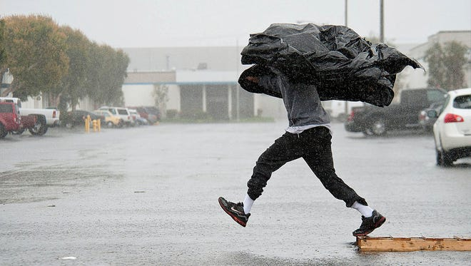 Manufacturing Assembly worker Terry Young, 24, of Rialto, Calif., uses a sheet of plastic to protect himself from a downpour.