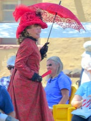 A lady in red stands out in the crowd at Fort Stanton