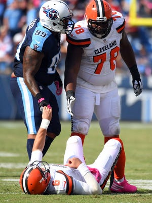 Cleveland Browns quarterback Cody Kessler (6) is helped up by Tennessee Titans defensive end Jurrell Casey (99) and offensive lineman Alvin Bailey (78) in the second half at Nissan Stadium. Tennessee won 28-26. Mandatory Credit: Christopher Hanewinckel-USA TODAY Sports