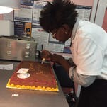 Lucy Rogers, owner of Sweet Lucy's Bakery in Monroe, puts the finishing touches on a graduation cake.