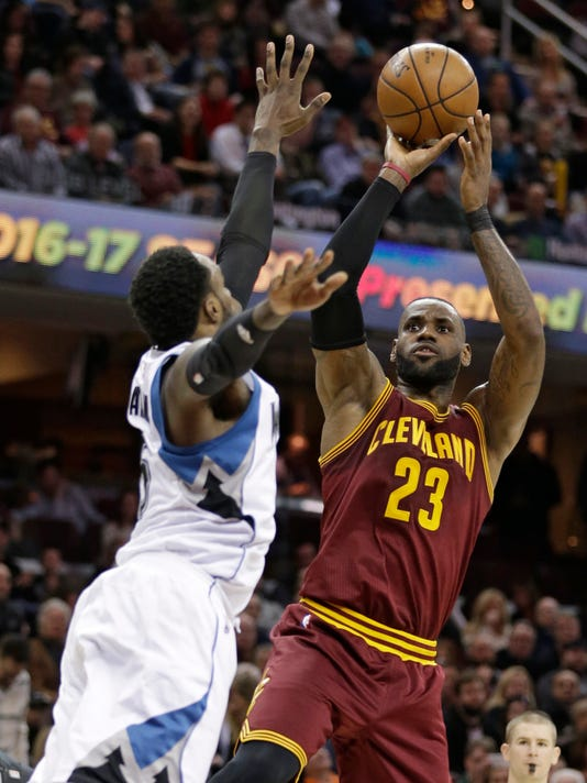 Cleveland Cavaliers' LeBron James, right, shoots against Minnesota Timberwolves' Shabazz Muhammad in the first half of an NBA basketball game, Wednesday, Feb. 1, 2017, in Cleveland. (AP Photo/Tony Dejak)