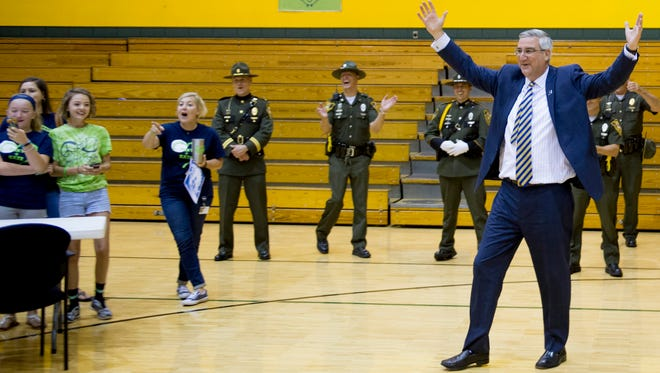 "Gov. Eric Holcomb celebrates 6-year-old Carlie Kuebler's 15-foot shot make on the basketball court at Sharon Elementary School in Newburgh, Ind., Monday morning.  Holcomb had earlier signed the ""Play for Kate"" bill into law."
