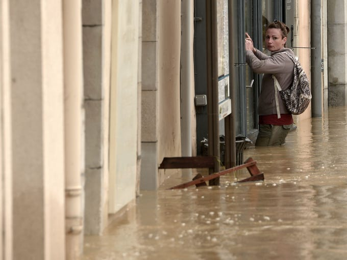 A woman stands in thigh-high flood waters outside a