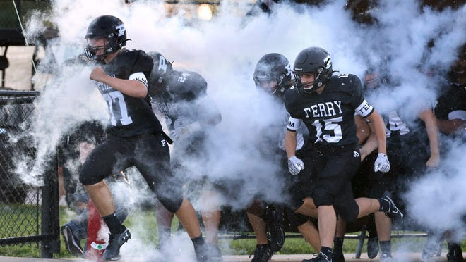 Justin Mattox (77) and Aiden Ellis (15) of Perry take the field prior to their game against Central Catholic at Perry on Friday, Sept. 4, 2020.