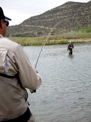 From left, Chris Gallegos puts tension on the line while Jay Walden seeks out a new spot while fly-fishing on May 18 on the San Juan River.