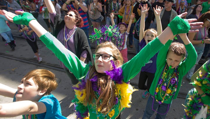 Elycia Cooley, center, and other revelers raise their