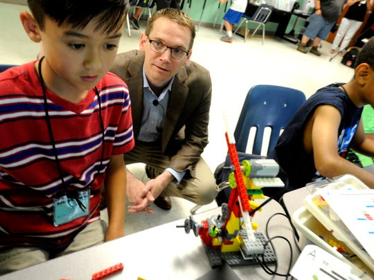 Texas Commissioner of Education Mike Morath talks to Cayden Bauer, 9, while he designs a wind turbine during the Abilene ISD Summer Technology Camp on Tuesday, June 6, 2017, at the ATEMS campus.