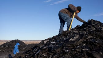 Darryl Sahmea (right) searches for quality pieces of coal at the Kayenta Mine in Black Mesa, Ariz., on Feb. 4, 2017. Many Hopi and Navjo tribe members rely on the free coal to heat their homes in the winter months.