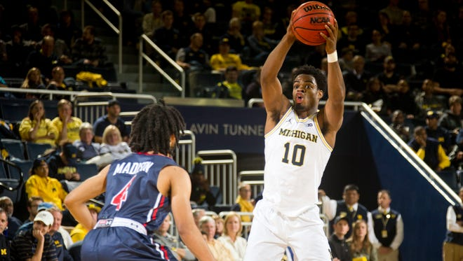 Michigan guard Derrick Walton Jr. (10) looks to pass the ball as he is defended by Howard guard Ausar Madison (4) in the first half Friday at Crisler Center.