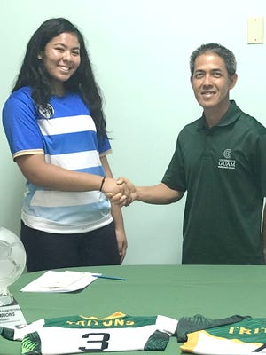 Aeryn Anulao shakes hands with Rod Hidalgo, the University of Guam's women's soccer coach after signing a letter of intent to play for the Tritons.