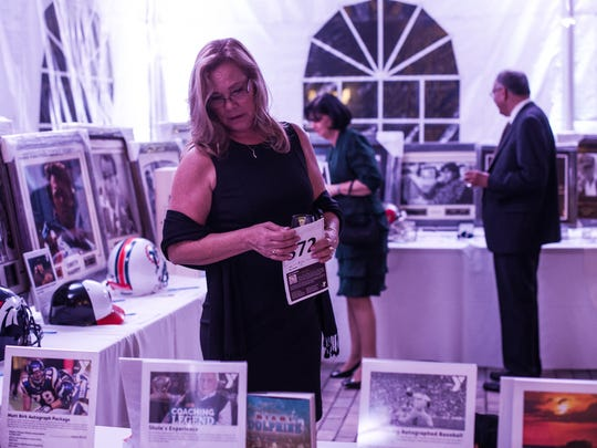 Meg Traina checks out items for auction during the YMCA's Gold Garden Gala at the Naples Botanical Garden in Naples, Fla., on Saturday, Feb. 18, 2017. The Gold Garden featured special guests, including Naples resident, and YMCA member Michelle Konkoly, who won multiple gold medals at the 2016 Paralympic Games in Rio de Janeiro, along with Dr. James Naismith Jr., the grandson of the inventor of basketball.
