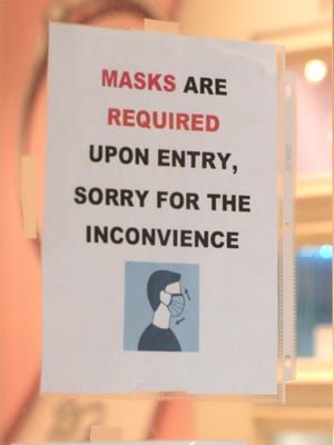 A sign on the door at Pandora alerts patrons about mask requirements at Summit Mall on Monday in Fairlawn.