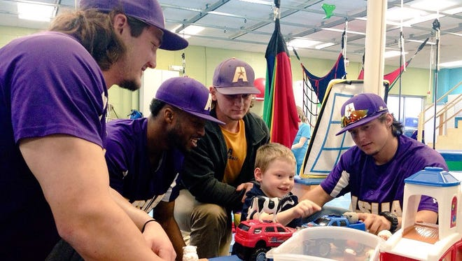 Louisiana State University of Alexandria baseball players (from left) Mark Traylor, Dominique Lincoln, Cody Arnaud and Trace Oliva play with Coen Davis, 5, after delivering toys to the Christus Cabrini Pediatric Therapy Center on Tuesday.