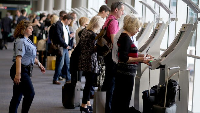 Passengers use the Automated Passport Control Kiosks set up for international travelers arriving at Miami International Airport on March 4, 2015 in Miami, Florida.