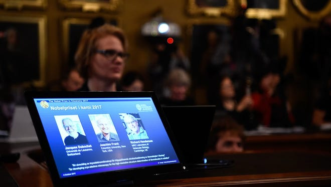 A laptop screen displays portraits of winners of the 2017 Nobel Prize in Chemistry on Oct. 4, at the Royal Swedish Academy of Sciences in Stockholm.