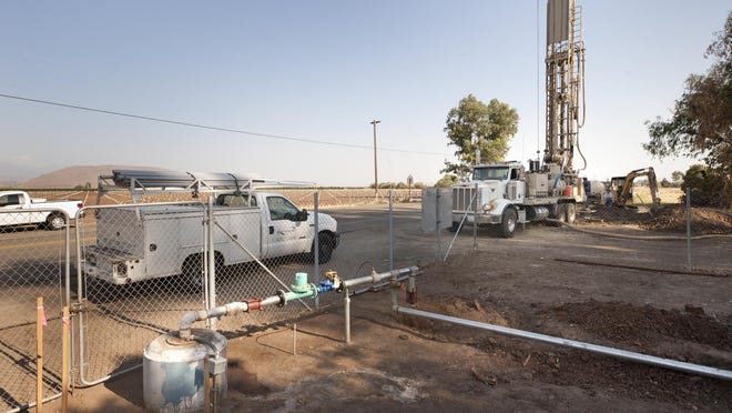 Workers with Belknap Pump Company drill for a new well in last year in Seville, a community in Tulare County in the Central Valley.
