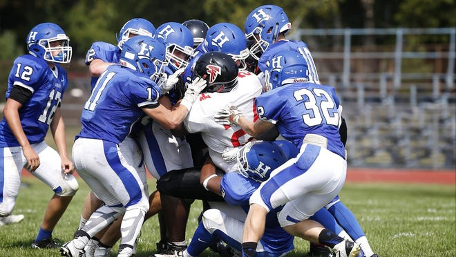 A swarm of Horseheads players tackle a Syracuse Fowler player during a victory in Week 1. That defense will face a bigger test Saturday against Binghamton.