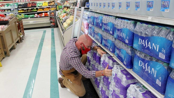 Piggly Wiggly manager Chris Creel arranges bottled water brought to front shelves as locals shop for grocery items in New Bern, NC, August 1, 2020. Select grocery and essentials purchases have increased in preparation for potential storm conditions with the forecast arrival of Hurricane Isaias.