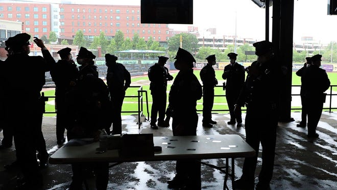 Cadets of the Akron Police Department Academy keep socially distanced as they await their graduation ceremony May 28 at Canal Park.