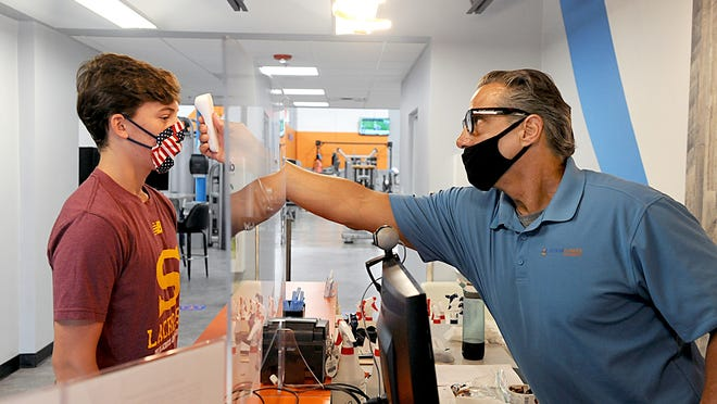 Frank Saldi, right, front desk associate at Evolve Fitness and Studios in Framingham, takes the temperature of Charlie David, 16, of Southborough, on Monday morning. Phase 3 of Massachusetts' reopening plan allows fitness clubs to reopen with new guidelines.