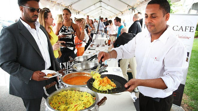 Dalwinder Singh serves dishes from Punjab Cafe, in Quincy at Father Bill's FoodFest in 2014.
