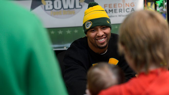 Green Bay Packers tight end Andrew Quarless is all smiles as he visits with fans during the Defeat Hunger Bowl at the Walmart Supercenter in De Pere.
