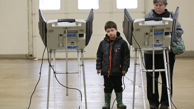 Lincoln Shipley, 4, waits as his grandmother, Mary Brisco, votes in the 2014 election Tuesday, November 4, 2014, at the Tippecanoe County Fairgrounds in Lafayette.