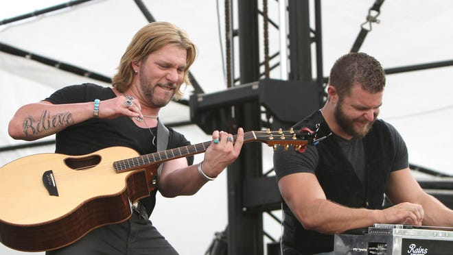 The Voice Season 7 Winner Craig Wayne Boyd, left, jams with steel guitar player Kyle Roop at the Countrylife Music Festival in Punta Gorda Friday.