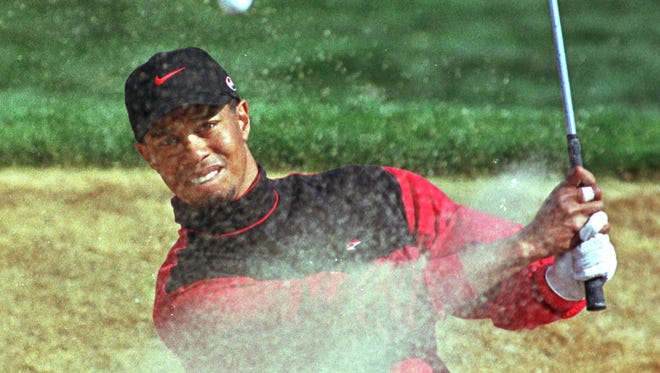 Tiger Woods hits a bunker shot on the third hole during the final round of the Phoenix Open in Scottsdale on Jan. 31, 1999. Woods will return after a 13-year absence to play in the 2015 Phoenix Open.