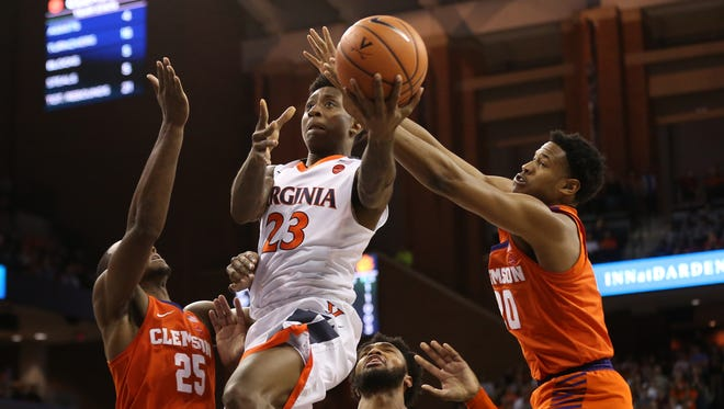 Virginia Cavaliers guard Nigel Johnson (23) shoots the ball as Clemson Tigers forward Aamir Simms (25) and Tigers forward Malik William (20) defend in the second half at John Paul Jones Arena.
