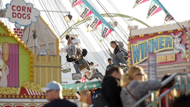 A woman works on a cell phone while riding the Wave Swinger ride in the background as other festival-goers wait in line to ride another attraction in the foreground on Sunday, February 20, 2011 at the Riverside County Fair and National Date Festival in Indio, Calif.