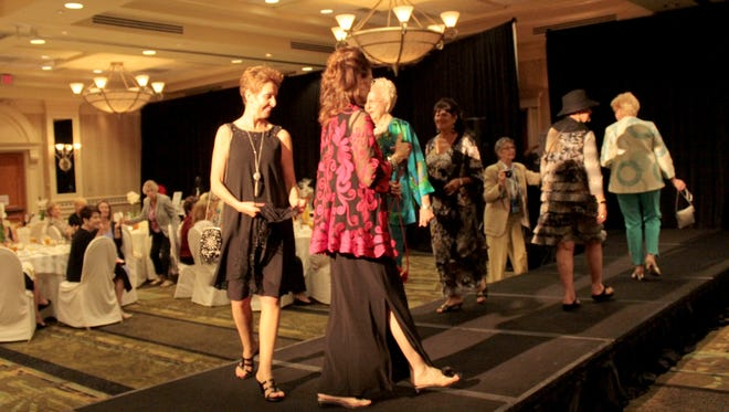 Women of the Ohio State Alumni Club of Naples take a final turn on the catwalk to close out the end of the Buckeyes Care fashion show.