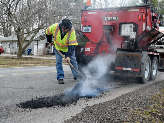A Noblesville street department worker patches a pothole.