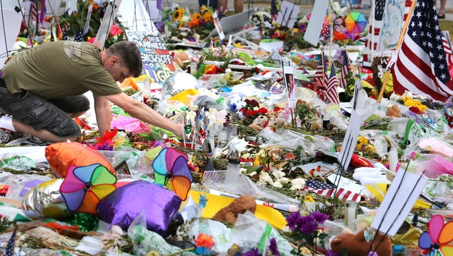 A visitor to the makeshift memorial for the victims of the Pulse night club shooting, relights a candle after an afternoon rain shower, at the Dr. Phillips Center for the Performing Arts, in downtown Orlando, Fla., Saturday.