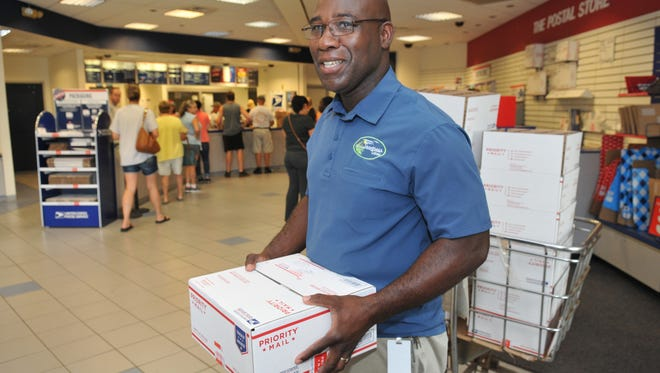 Michael McLean, who came over on his lunch break is mailing a care package to nephew, who is in the Air Force. Brevardians mailing holiday packages and mail at the West Melbourne post office. Monday is considered the busiest day of the year for the United States Post Office.