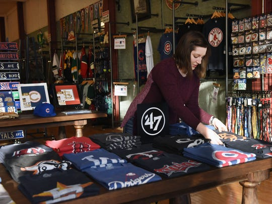 Kathryn Macziewski, owner of A League of Your Own, straightens out merchandise in her downtown store in this 2017 file photo.