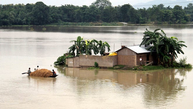 Indian villagers move in a boat through a flooded village in Morigaon district of northeastern Assam state, India, on Monday, Aug. 18, 2014.