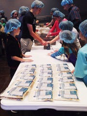 Members of Fellowship Bible Church in Jackson work to pack 20,000 meals for Haitian orphans.