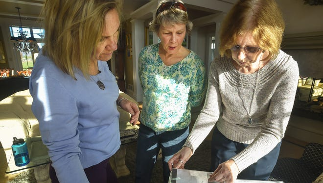 Patrice Nitterhouse, left, Tanya Nitterhouse, center, and Wanda Nitterhouse look at a binder full of information about the Nitterhouse family during Thanksgiving on Thursday, Nov. 26, 2015 in Chambersburg, Pennsylavania. Wanda Nitterhouse has been doing research on her family genealogy for over a year.