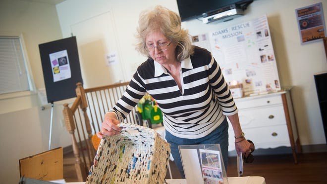 Kay Walters puts a bid on a basket made of recycled paper at the Upcycled Art Show & Auction at Agape House on April 17, 2016 in Gettysburg.