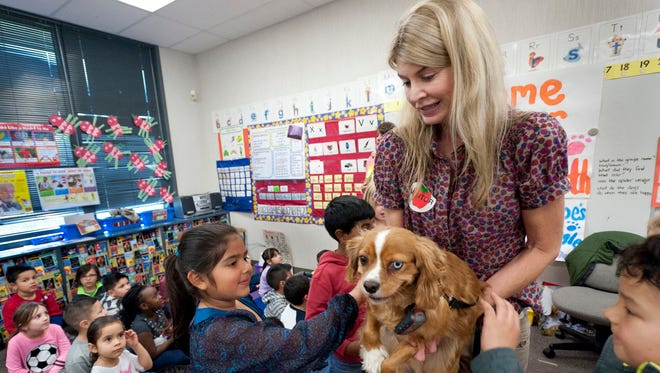 "Cheryl Smith, Tulare County public defender and author of a book about dogs' impact in mental health court, shares her dog Buster with Chloe Mejia, 6, and other kindergartners at Crestwood Elementary School on Tuesday, March 3, 2015. Each of the students received a copy of her book ""Oliver's Heroes: The Spider Adventures."""