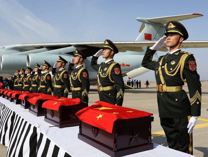 Chinese soldiers salute after carry coffins containing
