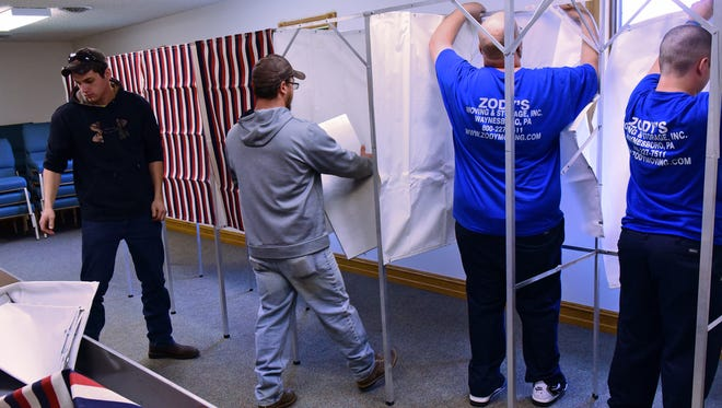 Employees from Zody's Moving and Storage and Franklin County maintenance help to set up voting booths Monday, April 25, 2016 at Cornerstone Church of Christ, Hamilton Township. Tuesday is primary election day in Pennsylvania.