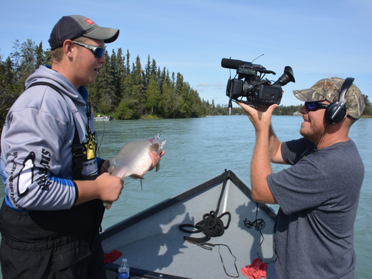 """Jake Romanack, left, conducts a TV interview while filming an episode of """"Fishing 411"""" on location in Alaska. Show producer Gabe VanWormer videotapes the action."""