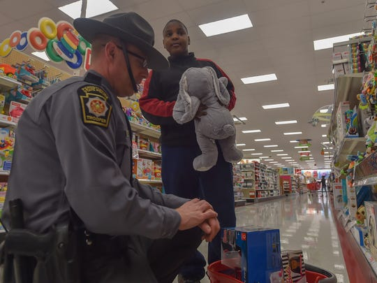 Michael Aldajuste, right, holds a stuffed bunny that State Trooper Robert Wareham found for Aldajuste little sister inside Target in Chambersburg on Tuesday, Dec. 8, 2015. Target and law enforcement officer get together to do Shopping with Cops.