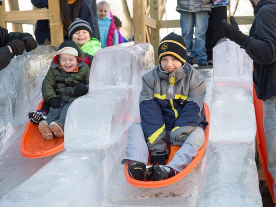 Brothers Blain and Evan Kauffman, left, ride together at the same time as Tyson Clerry, right, sleds down the ice slide at IceFest on Saturday, Jan. 30, 2015 in Chambersburg, Pa. The ice slide is one of the most popular attractions at IceFest.